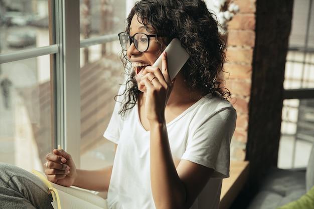 Mulher afro-americana freelancer durante o trabalho em um escritório doméstico durante a quarentena