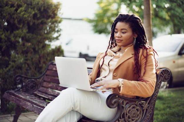 Mulher afro-americana freelancer sentada em um banco em uma rua e usando um laptop