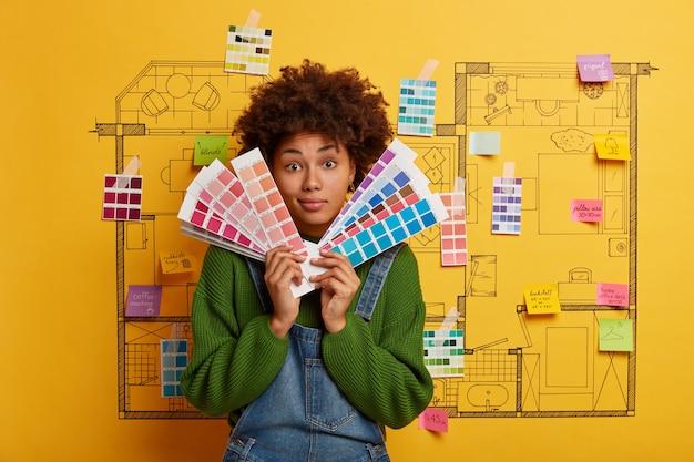 Mulher afro-americana guarda amostras de cores para novo apartamento