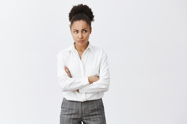 Mulher afro-americana indecisa com os braços cruzados no peito e carrancuda, olhando bem com expressão preocupada