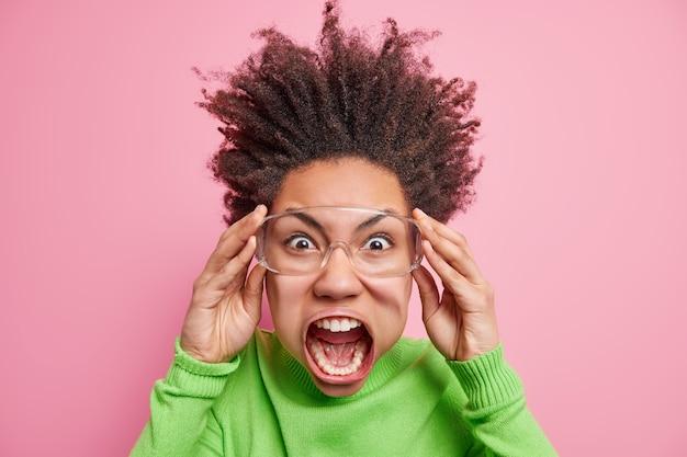 Mulher afro-americana indignada com o cabelo arrepiado grita alto de raiva sendo superemocional e louca usa óculos grandes transparentes com gola rolê verde enlouquece. conceito de emoções e pessoas