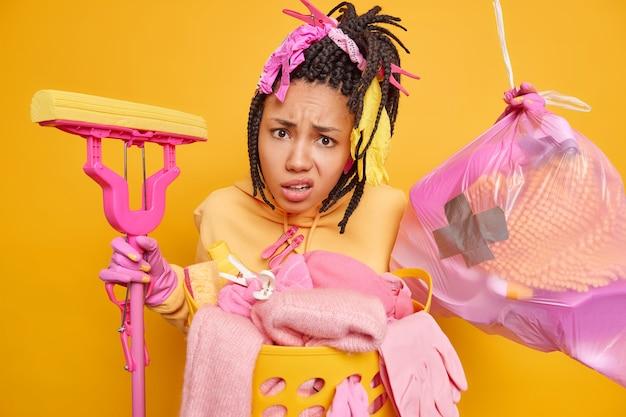 Mulher afro-americana indignada fazendo poses de dreadlocks com lixo