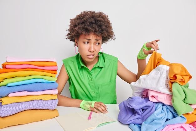 Mulher afro-americana insatisfeita pega roupas sujas em pilhas de roupas na lavanderia, faz anotações em poses de caderno contra uma parede branca, sente que a aversão tem rosto nojento. grande conceito de lavagem
