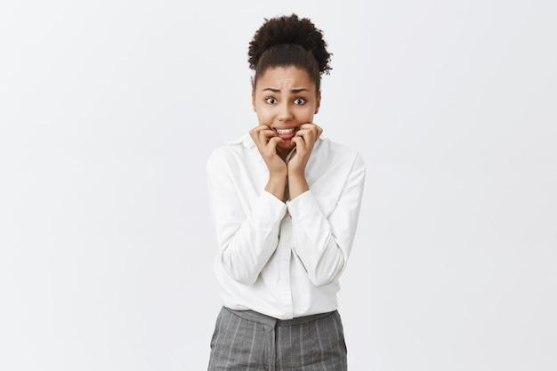Mulher afro-americana insegura e preocupada roendo as unhas, tenho grandes problemas