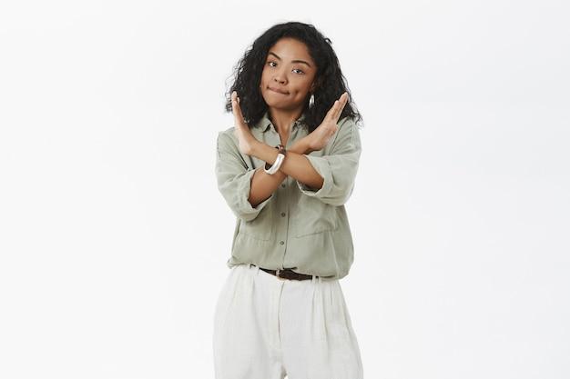 Mulher afro-americana intensa e irritada com cabelo encaracolado franzindo os lábios e fazendo cruz com os braços