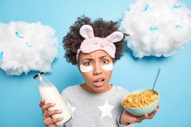 Mulher afro-americana intrigada e indignada come cereais no café da manhã, bebe leite fresco e usa macacão de máscara de dormir isolado sobre a parede azul