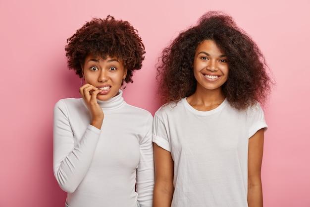 Mulher afro-americana intrigada e nervosa morde as unhas, parece preocupada com a câmera, sua alegre amiga com cabelos crespos e crespos está perto, usa roupas brancas, expressa emoções diferentes