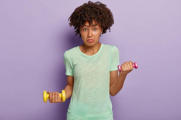 Mulher afro-americana intrigada parece surpreendente, segura dois halteres, trabalha os músculos, veste camiseta, gosta de fitness e esporte, isolada na parede roxa. senhora com pesos treina na academia