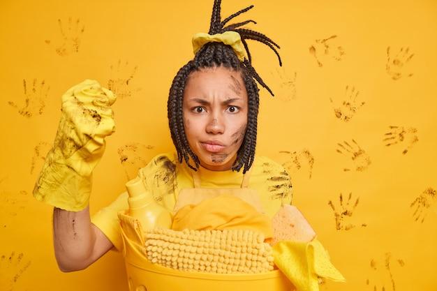 Mulher afro-americana irritada fecha o punho olhando com raiva para a câmera poses sujas perto da cesta de roupa suja penteada com dreadlocks isolados sobre a parede amarela