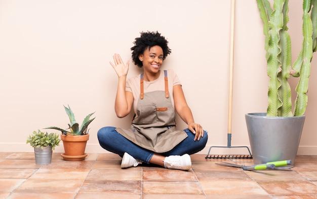 Mulher afro-americana jardineiro sentado no chão