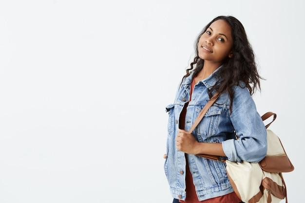 Mulher afro-americana jovem bonita positiva positiva com cabelo ondulado escuro adorável sorrindo na jaqueta jeans e camiseta vermelha com mochila no ombro, posando na parede