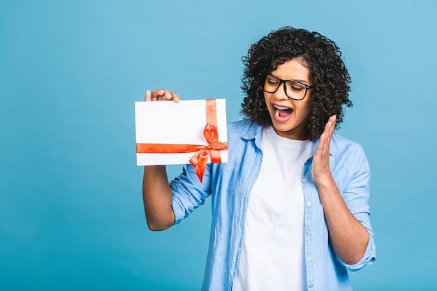 Mulher afro-americana jovem encaracolada chocada e surpreendida isolada no retrato de estúdio de fundo azul. simule o espaço da cópia. segurando um certificado de presente.