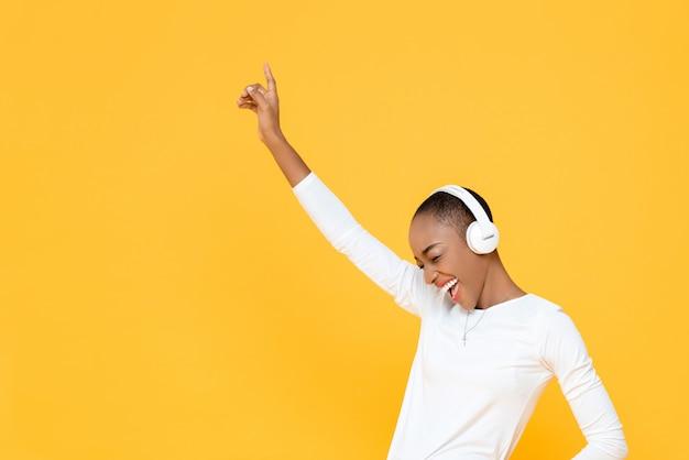 Mulher afro-americana jovem feliz, levantando a mão enquanto ouve música em fones de ouvido sem fio na parede isolada amarela