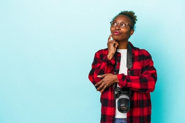 Mulher afro-americana jovem fotógrafo isolada sobre fundo azul, olhando de soslaio com expressão duvidosa e cética.
