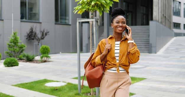 Mulher afro-americana linda feliz sorriu falando no celular e andando lá fora. mulher alegre falando no celular e passeando. conversa telefônica.