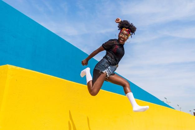 Mulher afro-americana linda jovem feliz pulando contra a parede enquanto sorrindo