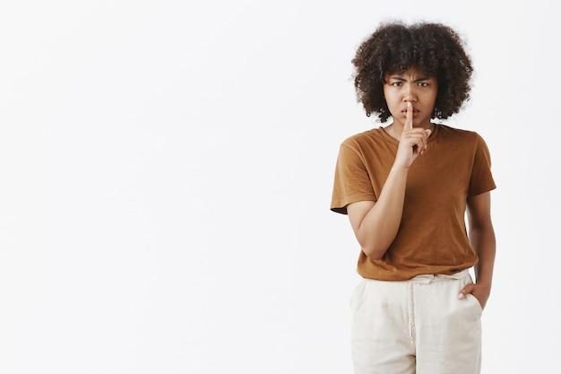 Mulher afro-americana mandona e insatisfeita com penteado afro franzindo a testa por não gostar de dizer shh, mostrando um gesto de silêncio com o dedo indicador sobre a boca fechada