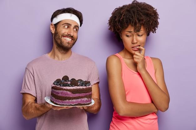 Mulher afro-americana mantém o dedo na boca, se sente tentada enquanto olha para um delicioso bolo de mirtilo