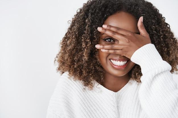 Mulher afro-americana meiga e fofa se escondendo atrás da palma da mão espiando por entre o dedo e sorrindo amplamente, antecipando a surpresa brincando e se sentindo feliz sobre a parede branca