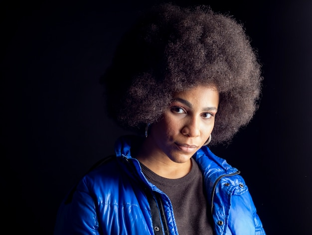 Mulher afro-americana, mestiça, posando em fundo escuro, roupas urbanas, moderna bonita e sorridente