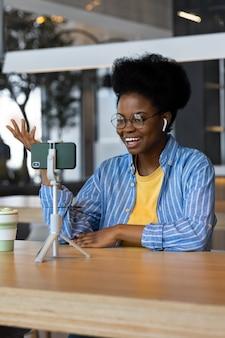 Mulher afro-americana milenar em um lugar público assistindo a um webinar ou conversando em uma webcam de