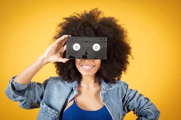Mulher afro-americana mista, cobrindo os olhos com uma fita de vídeo retrô na mão com fundo amarelo, copie o espaço