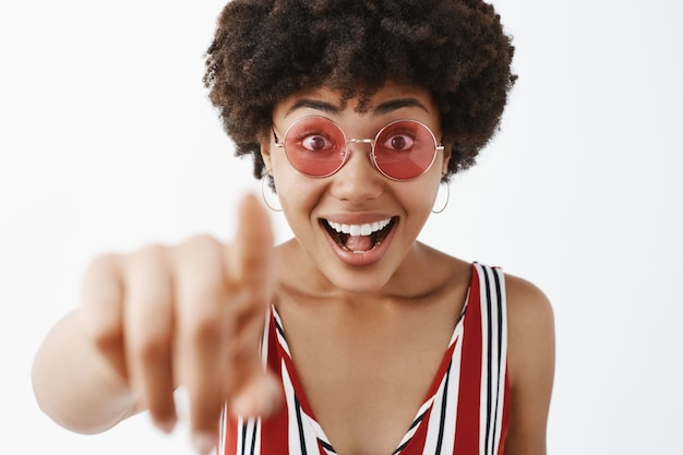 Mulher afro-americana moderna, atraente e elegante, divertida em uma blusa listrada, puxando a mão e apontando, parecendo impressionada e animada com o conceito incrível