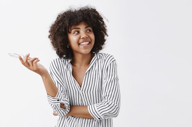 Mulher afro-americana moderna, feliz e despreocupada, com uma blusa listrada da moda, óculos na mão e olhando para o canto superior direito com um sorriso largo e satisfeito