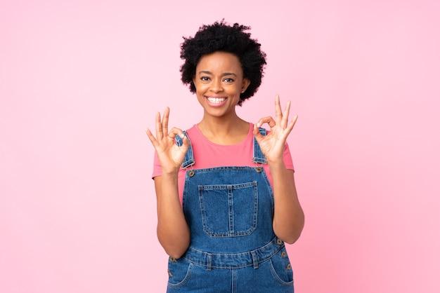 Mulher afro-americana mostrando sinais de ok isoladas em fundo rosa