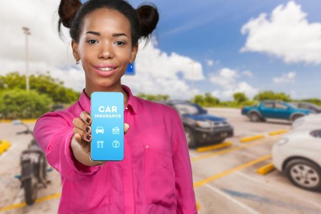 Mulher afro-americana, mostrando um telefone móvel