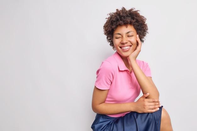Mulher afro-americana muito feliz, de cabelos cacheados, sorri com os dentes e mantém os olhos fechados, vestida com uma camiseta rosa casual e saia isolada sobre a parede branca