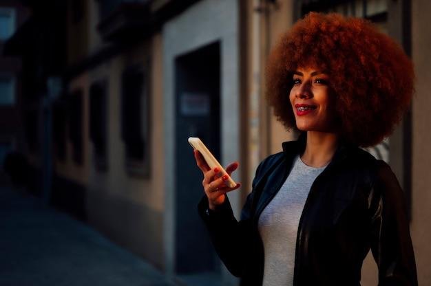 Mulher afro-americana na cidade com o telefone na mão