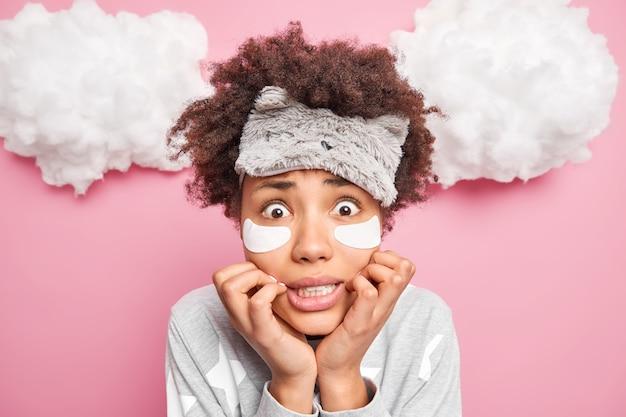 Mulher afro-americana nervosa e estressada parece envergonhada ao ver a câmera treme de medo desperta depois de ver olhares de sonho terríveis preocupados vestida com pijamas posa sozinha dentro de casa