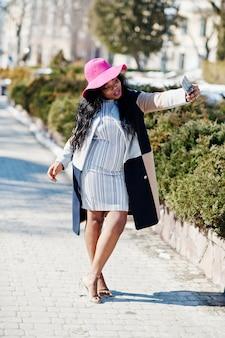 Mulher afro-americana no chapéu e casaco com telefone andando nas ruas.
