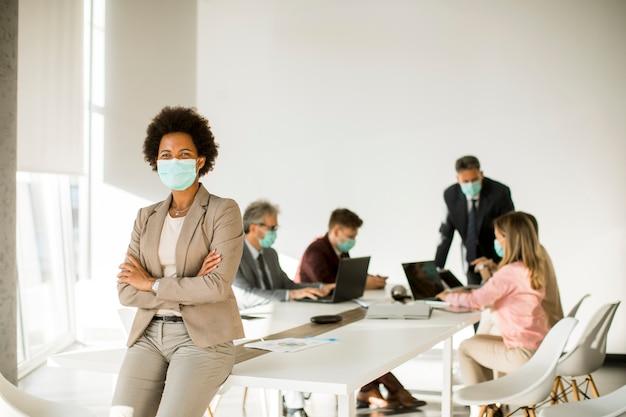 Mulher afro-americana no escritório usar máscara como proteção contra coronavírus