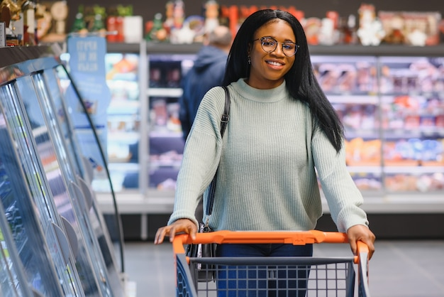 Mulher afro-americana no supermercado com carrinho de compras.