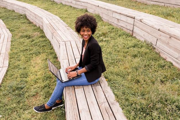 Mulher afro-americana nova bonita que usa o portátil, sentando-se nas escadas de madeira e sorrindo. fundo de madeira. estilo de vida ao ar livre