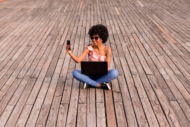 Mulher afro-americana nova bonita que usa o portátil, sentando-se no assoalho de madeira e sorrindo. fundo de madeira. estilo de vida ao ar livre
