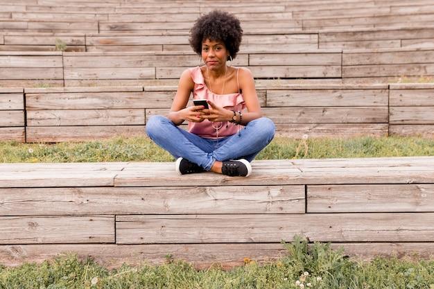 Mulher afro-americana nova bonita que usa o telefone móvel, sentando-se nas escadas de madeira e sorrindo. fundo de madeira. estilo de vida ao ar livre