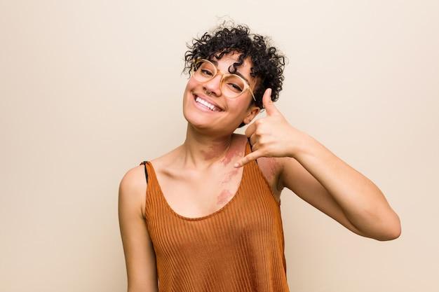 Mulher afro-americana nova com a marca de nascimento da pele que mostra um gesto de chamada de telefone móvel com os dedos.