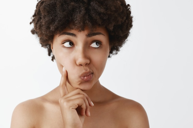 Mulher afro-americana nua, tenra e feminina, com cabelos cacheados, tocando a bochecha, virando os lábios para a direita e olhando para cima enquanto pensa ou decide algo