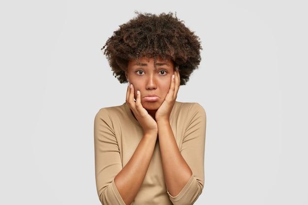 Mulher afro-americana ofendida e descontente com cabelo crespo e espesso, curva os lábios, mantém as mãos nas bochechas, fica com raiva do amante, espera por desculpas, posa contra uma parede branca. pessoas, conceito de emoções