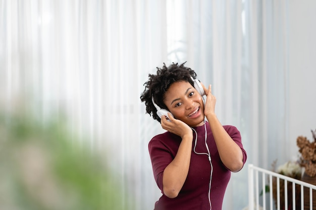 Mulher afro-americana ouvindo música com fones de ouvido na sala de estar