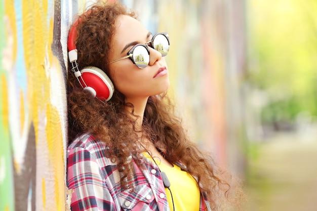 Mulher afro-americana ouvindo música em fones de ouvido na rua