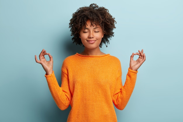Mulher afro-americana pacífica e atenta medita dentro de casa, mantém as mãos em gestos de mudra, tem os olhos fechados