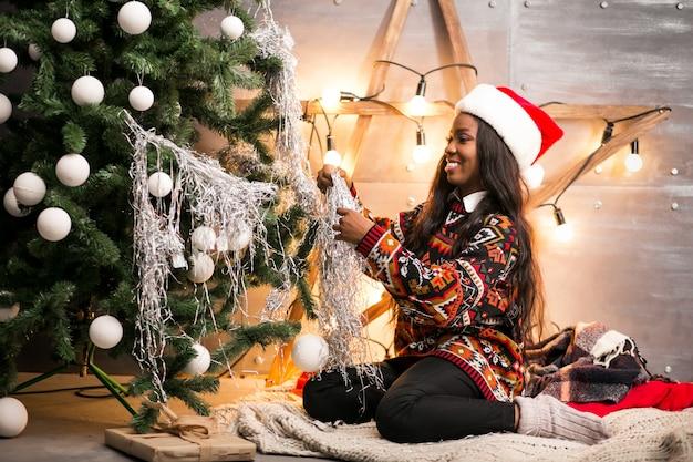Mulher afro-americana pendurada brinquedos em uma árvore de natal