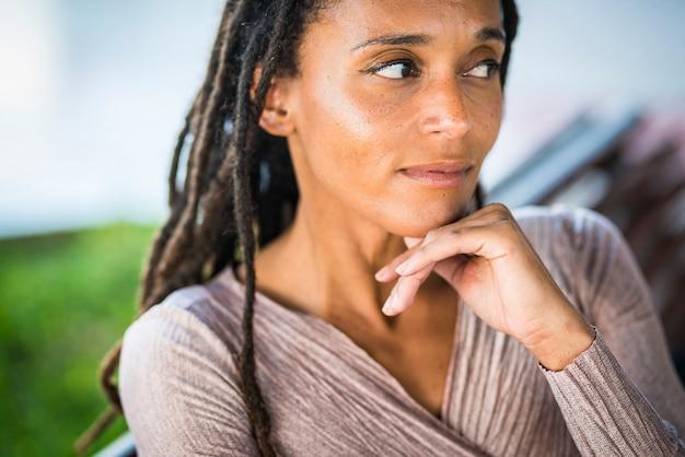 Mulher afro-americana pensativa com a mão no queixo mulher negra com penteado deadlocks