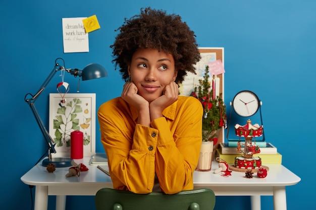 Mulher afro-americana pensativa e contemplativa se senta na cadeira, segura o queixo, olha pensativamente para o lado, estuda em seu próprio armário aconchegante em casa