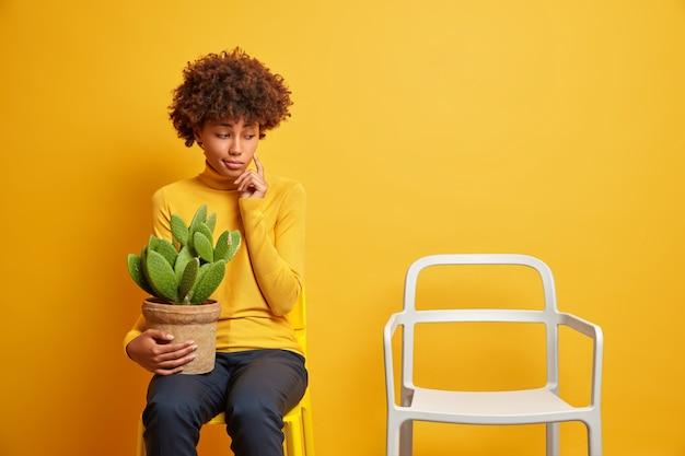 Mulher afro-americana pensativa, pensativa, concentrada em uma cadeira vazia, segurando um vaso de cacto, sentindo-se solitária, usando roupas casuais