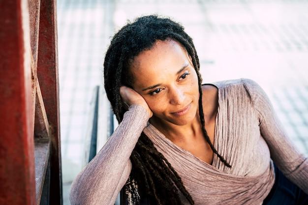 Mulher afro-americana pensativa, sorrindo com a cabeça na mão. mulher negra com penteado deadlocks. jovem mulher sentada no banco do parque. mulher elegante com dreadlocks sonhando ao ar livre no banco